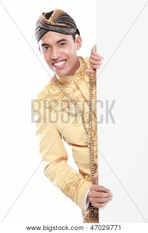 Homem vestindo trajes tradicionais de Java me esconder atrás de placa branca em branco