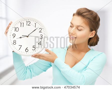 attractive woman holding wall clock in her hands