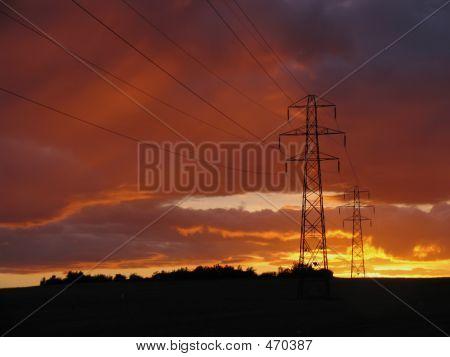 Torres de electricidad contra una puesta de sol
