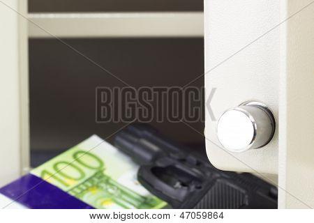 Money and a gun in the front of a safe