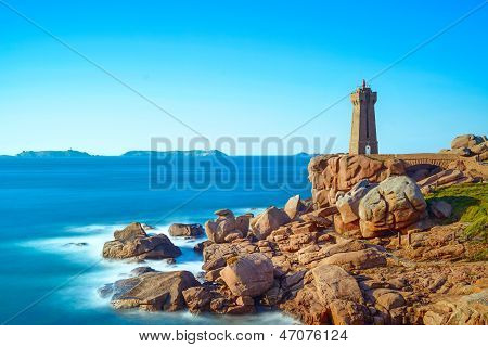 Ploumanach Mean Ruz lighthouse red sunset in pink granite coast Perros Guirec Brittany France. Long exposure. poster
