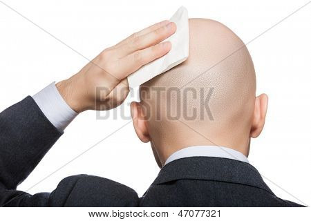Tired or upset businessman wiping or drying bald sweat head with handkerchief or tissue