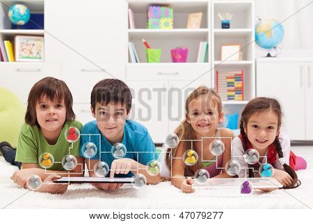 Happy kids connecting to social networks and friends - using tablet computers
