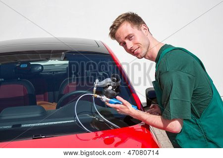 Glazier repairing windshield on a car after stone-chipping damage poster