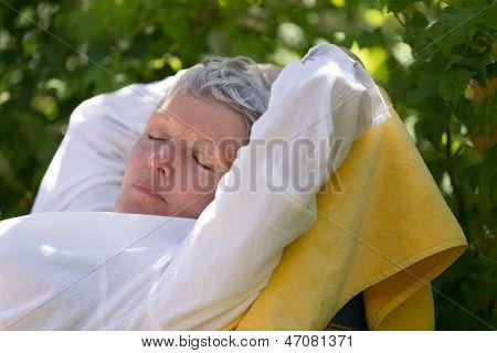 Senior Woman Sleeping On Lounger