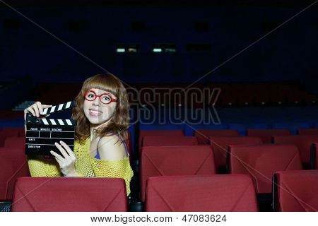Happy beautiful woman in red glasses holds clap board in movie theater.