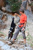 Rock climber feeding a goat at a cliff poster