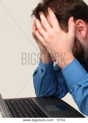 Man Frustrated In Front Of Laptop Computer