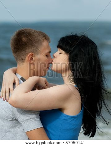 Girl is kissing her teenage boyfriend outdoors poster