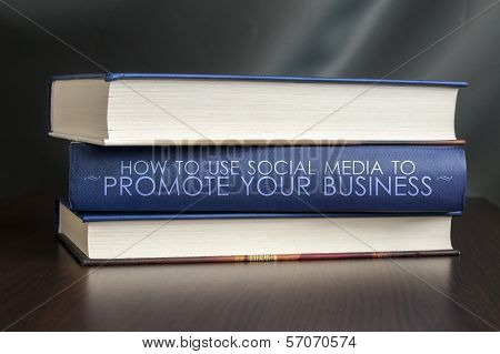 "Books on a table and one with "" Use social media to promote your business. "" cover. Book concept. poster"