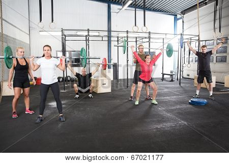 Team workout with weights at fitness gym center