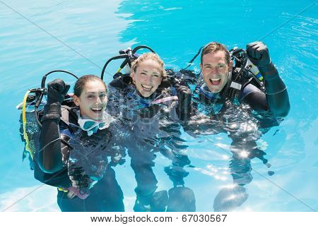 Smiling friends on scuba training in swimming pool cheering at camera on a sunny day