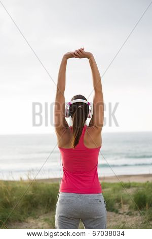 Fitness Female Athlete Stretching Arms Towards The Sea