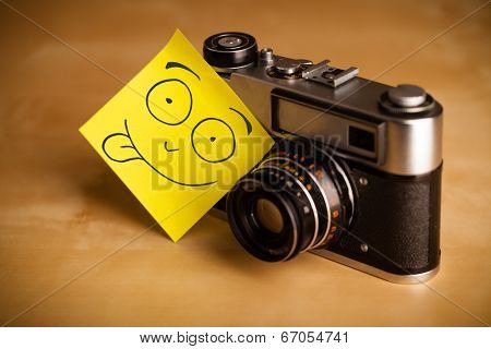 Drawn smiley face on a post-it note sticked on an old photo camera