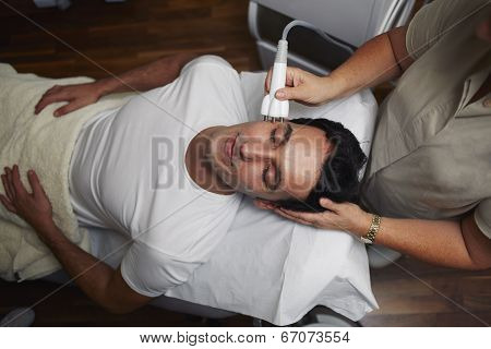 Handsome male patient having a laser skin treatment