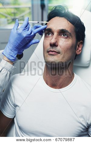 Attractive man giving facial injections in aesthetic clinic