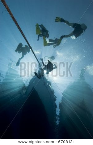 Silhouette Of Divers And Dive Boat.