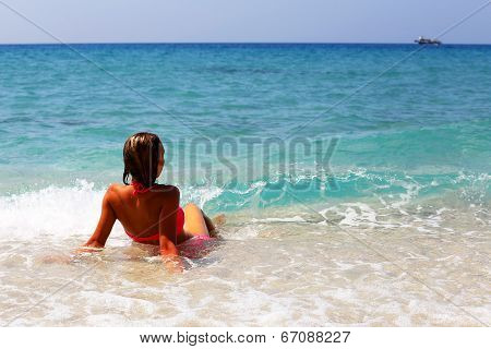 Back View Of Beautiful Woman Sitting On The Beach