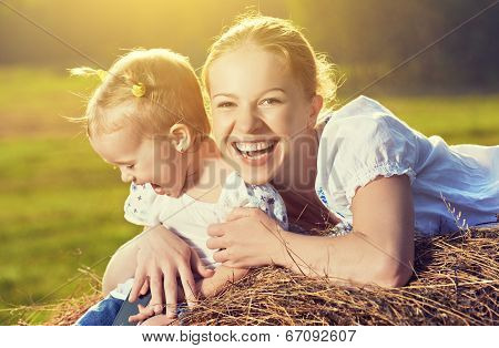 Happy Family In Summer Nature. Mother And Baby Daughter In The Hay, Straw