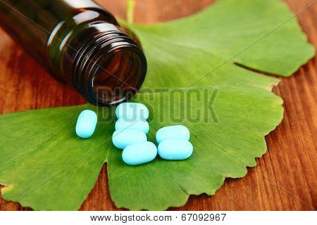 Ginkgo biloba leaves and medicine bottle on wooden background