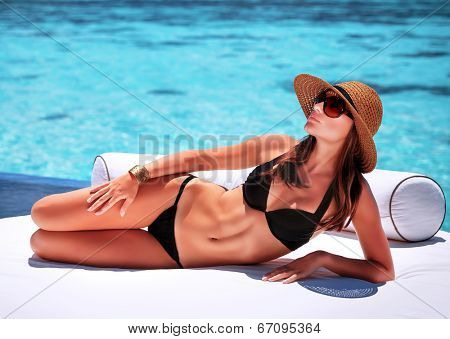 Sexy woman tanning on the beach, lying down on white luxury sofa, spending summer holidays on Maldives resort