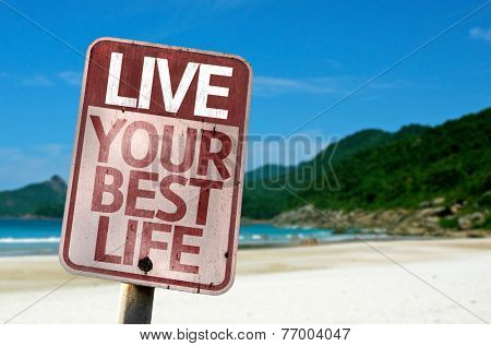 Live Your Best Life sign with a beach on background