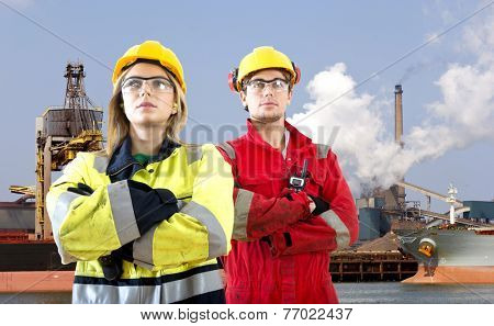 Two logistical engineers, making a stance in front of an raw material transhipment plant poster