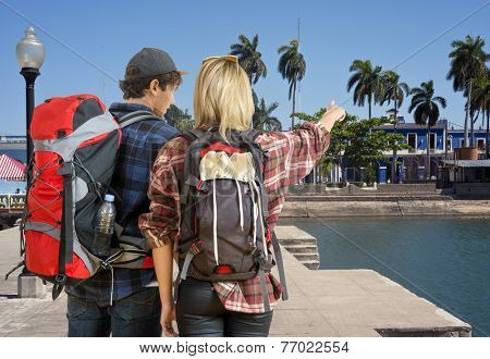 Young couple, arriving at a tropical resort, looking for a place or hostel to stay