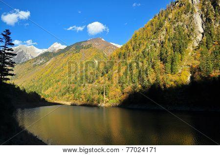 Scenic view of mountain at Jiuzhaigou with contrastingly dark lake. poster