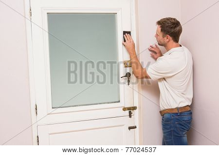 Man hand sanding the door before refinishing at home