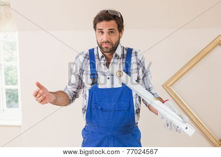 Confused construction worker holding spirit level in a new house