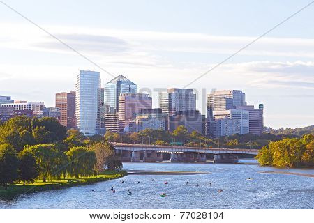 River before sunset with city skyline on background.