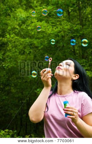 Frau bläst Seifenblasen colorful