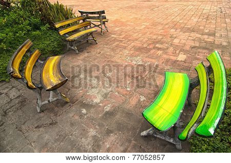 Few Colorful Benches Oposit Each Other On A Brick Square - Traditional Thailand
