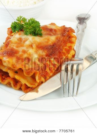 Lasagna With Fork And Knife On White