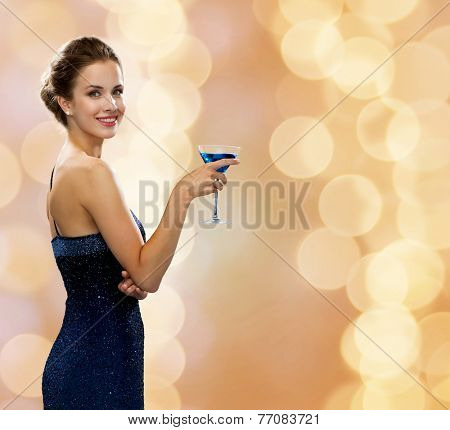 party, drinks, holidays, luxury and celebration concept - smiling woman in evening dress holding cocktail over beige lights background
