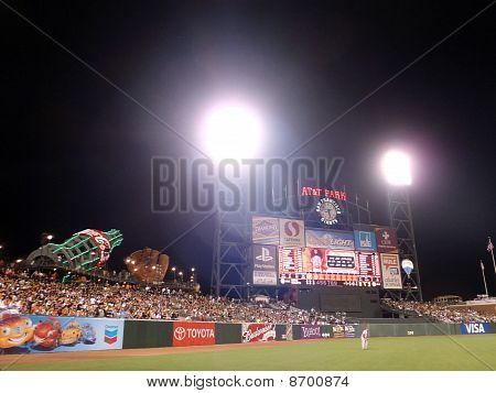 Reds Outfielder Stands In Left Field Ready For Play During Night Game