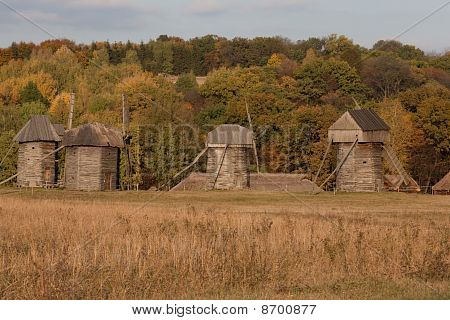 Picturesque Autumnal View. Four Windmills In The Field. Forest And Sky In The Background.