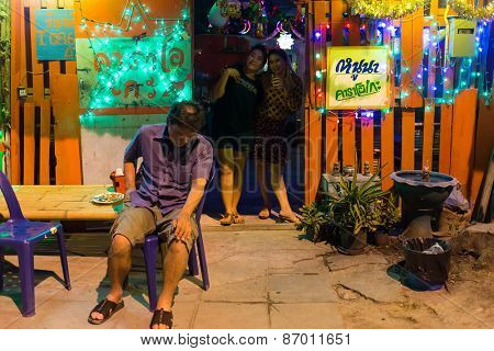 LAEM CHABANG, THAILAND, DECEMBER 26:A drunk and tired man is sitting in front of a traditional Thai Karaoke wooden house in the city of Laem Chabang, Thailand.
