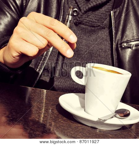 closeup of a young man with an electronic cigarette and a cup of coffee in the terrace of a cafe