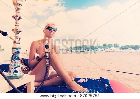 Woman with hookah on the beach in bikini poster
