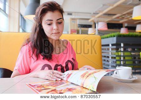 Pretty woman looking at the menu at a restaurant