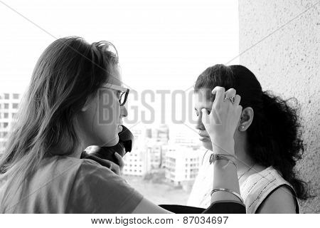 Indian woman photographer wearing glasses retouching makeup of the model holding camera in hand. black and white photo poster
