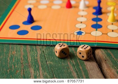 Two Wooden Dices In Front Of Ludo With Figurines