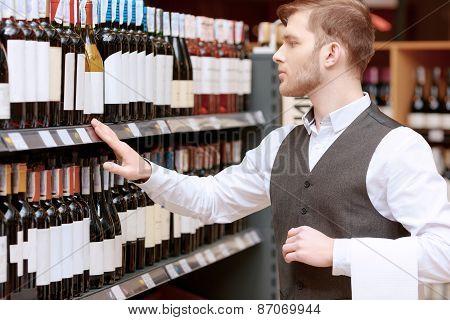 Sommelier in the store near shelves
