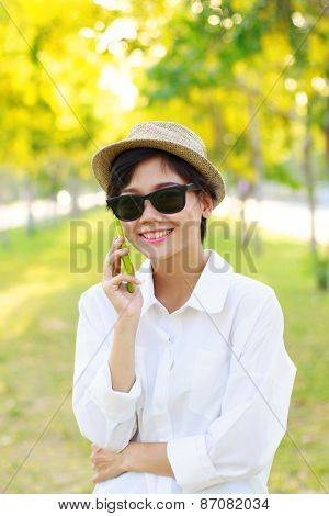 Young Beautiful Woman Wearing Sun Glasses And Fashion Straw Hat Talking On Mobile Phone With Happy F