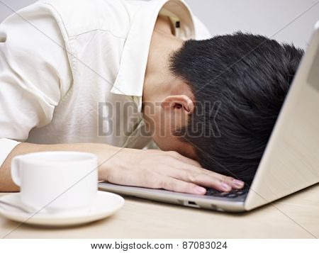 frustrated asian young man buries his head in the keyboard of a laptop computer. poster