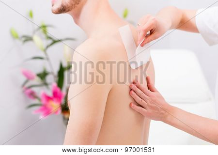 man receiving waxing for hair removal in beauty parlor