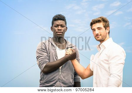Afroamerican And Caucasian Men Shaking Hands In A Modern Handshake To Show Each Other Friendship