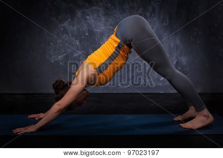 Beautiful sporty fit yogini woman practices yoga asana adhomukha svanasana - downward facing dog pose on dark  background